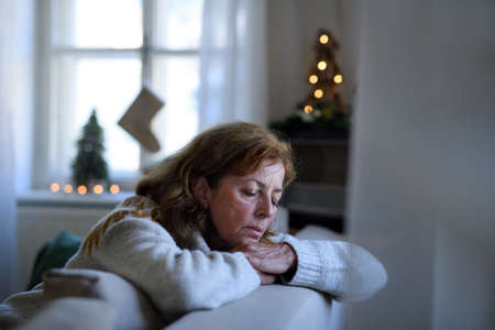 Lonely senior woman sitting and sleeping on sofa indoors at Christmas, solitude concept.
