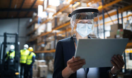 Photo for Manager with protective shield using tablet indoors in warehouse, coronavirus concept. - Royalty Free Image