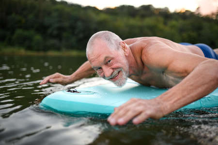 Photo pour Senior man on paddleboard on lake in summer, swimming. - image libre de droit