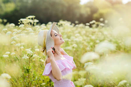 Photo for A girl in a straw hat is resting in nature. A young woman smiles, raising her face to the sun. Summer vacation concept. - Royalty Free Image