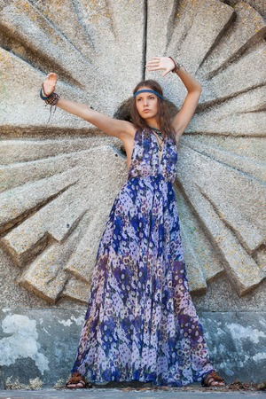 Young woman in a sundress at the stone wall