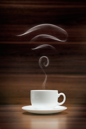 Cup of coffee with wi-fi icon shaped smoke on dark wood background