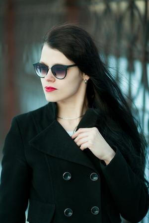 Photo pour Young woman posing in black coat and black hat. - image libre de droit