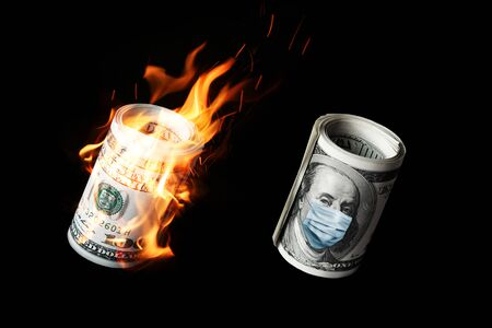 Photo pour COVID-19 coronavirus in USA. Roll of hundred dollars money bill with face mask and in fire. - image libre de droit