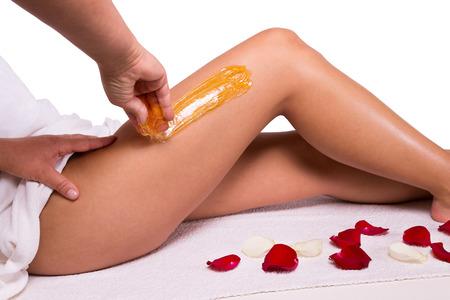 Photo pour Sugaring: epilation with liquate sugar at legs. - image libre de droit
