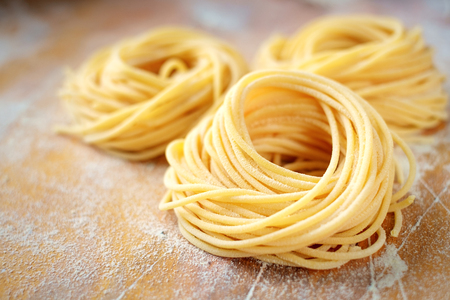 Photo for raw homemade spaghetti nest with flour on a wooden table. fresh Italian pasta - Royalty Free Image