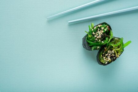 Two Chuka seaweed Sushi with chopsticks on a blue background, top view