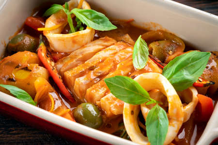 Photo pour Cod stewed with vegetables and Basil in tomato sauce in a deep dish, close up - image libre de droit
