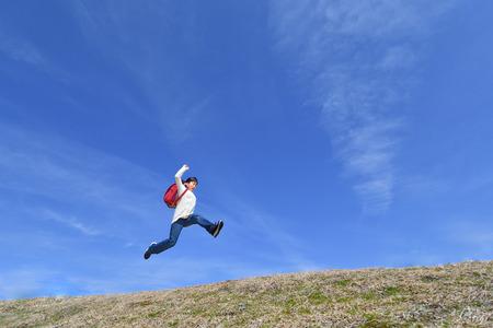 Foto de Japanese elementary school girl jumping in the blue sky - Imagen libre de derechos