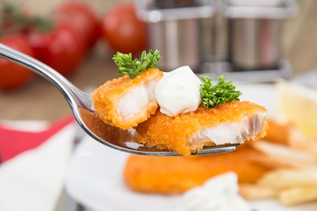 Pieces of fried Fish on a fork with lunch in the background