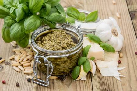 Fresh made Pesto Sauce in a glass on wooden background