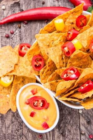Bowl with Nachos and Cheese Sauce on wooden background