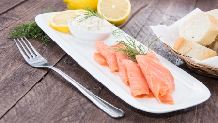 Plate with Salmon on wooden background