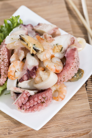 Portion of Seafood Salad (close-up shot) with squid, mussels and prawns