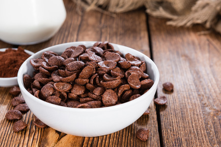 Portion of sweet breakfast (choco flakes) on wooden background