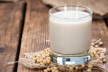 Soy Milk with some Seeds (close-up shot) on wooden background
