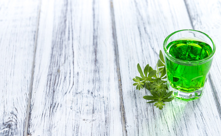 Woodruff Liqueur in a small glass (on wooden background)