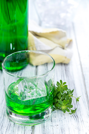 Woodruff Liqueur in a small shot glass (on wooden background)