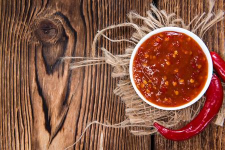 Portion of Chili Sauce (Sambal Oelek) on rustic wood