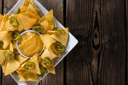 Nachos with Cheese Sauce (close-up shot) on wooden background
