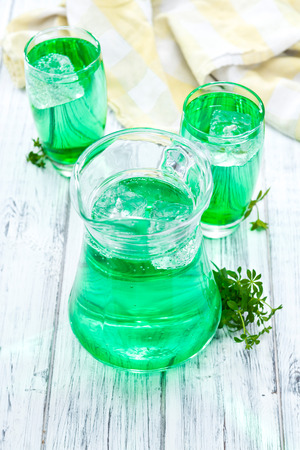 Sparkling Woodruff Drink in a glass (on bright wooden background)