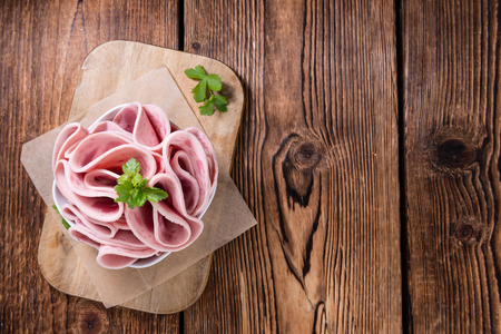 Cutted Ham Sausage on wooden background (selective focus)