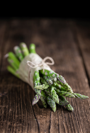 Fresh green Asparagus (selective focus, close-up shot) on wooden background