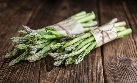 Portion of green Asparagus (close-up shot) on wooden background