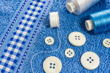 background top view group of sewing tools are as follows white and blue threads, bobbin, big and small white buttonlay on blue towel
