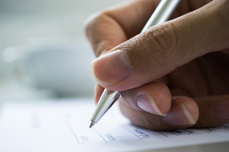 hand with pen over checklist form