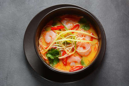Photo pour Laksa Soup – a Malaysian  Coconut Curry  Soup with shrimps over rice noodles topped with fresh bean spouts,cucumber, lime, red chili pepper and cilantro - image libre de droit