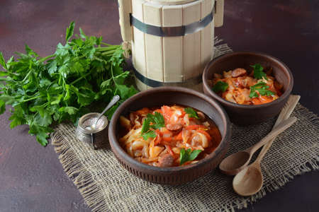 Photo for Cabbage stew with grilled sausage in tomato sauce - traditional dish of German,  Polish or Russian  cuisine - Royalty Free Image