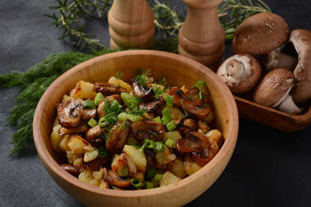 Photo pour Fried potatoes with mushrooms in a wooden bowl. Rustic style. - image libre de droit