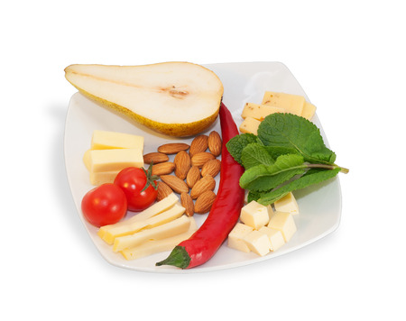 White cheese plate with almonds, red peppers, cherry tomatoes, mint leaves isolated on white background