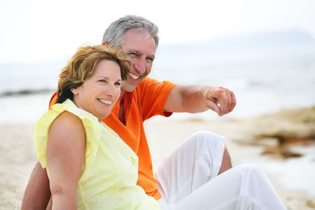 Happy mature couple sitting on the beach. の写真素材