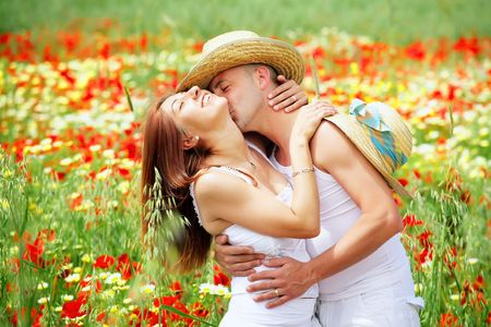 Young happy couple on a meadow full of poppies.
