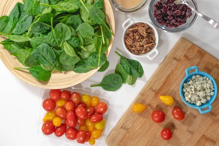 Photo for Salad ingredients close up, view from above.  Spinach, tomatoes, blue cheese, pecans, cranberries, and dressing on a kitchen table - Royalty Free Image