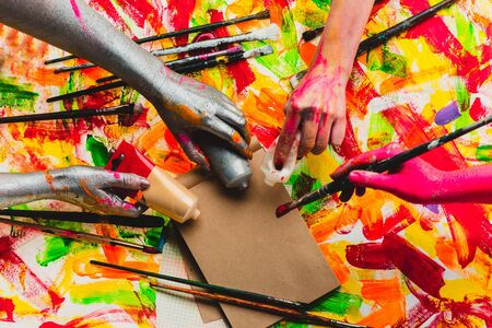 Photo pour Creative project. Beautiful background. Art. The collective. Team building. Four colored hands. Multi-color photo. Central composition. Filling the space. Work and fun. - image libre de droit