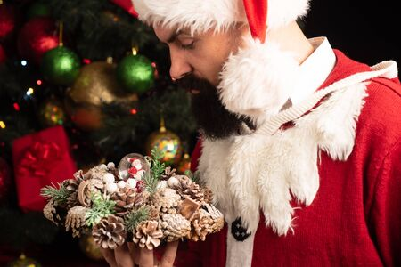 Photo pour Santa with Christmas decorations. Attractive man holding a christmas wreath in his hands. Holidays. - image libre de droit