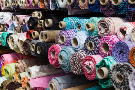 fabric rolls at market stall - textile industry background