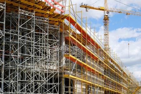 Photo pour New building construction stite - scaffolding and crane on building site - image libre de droit