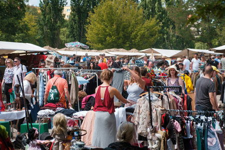 Photo for Girls looking for clothes and fashion on crowded flea market in Berlin, Germany - Royalty Free Image