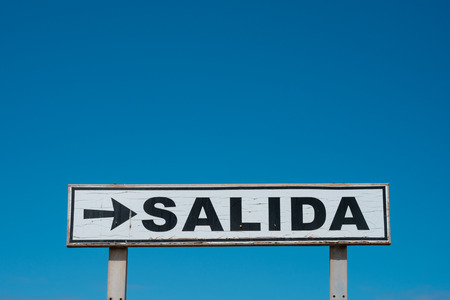 Exit sign (spanish: SALIDA) isolated on blue sky