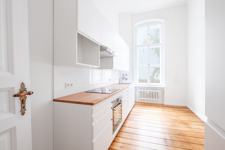 Foto per empty, new  built-in kitchen with white furniture and wooden floor - - Immagine Royalty Free