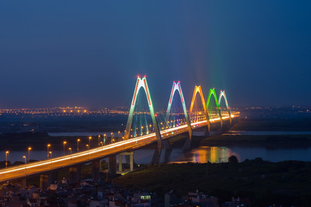 Aerial skyline view of Nhat Tan bridge crossing Red River at twilight. Hanoi cityscape