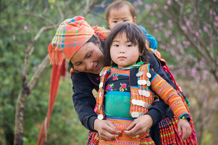 Son La, Vietnam - Jan 13, 2016: H'mong girl child wearing traditional clothes with her mother in Ta Xua village, Bac Yen district