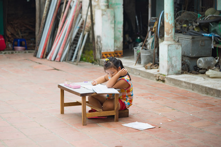 Dong Anh, Hanoi, Vietnam - Sep 20, 2015: Schoolgirl do homework  on table on yard in front of her house. Lacking of good education condition is a problem of Asian developing countries