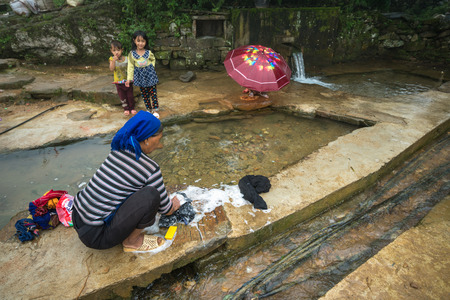 Lao Cai, Vietnam - Sep 7, 2017: Ethnic minority woman washing clothes at water supply in Y Ty, Bat Xat district