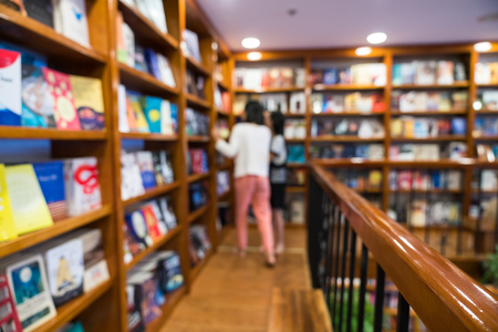Blurred abstract background of bookshelves in book store, with a girl finding book in the store.