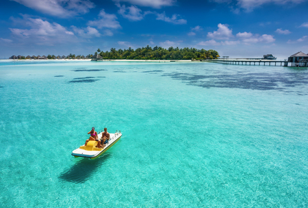 Foto de Couple on a floating pedalo boat is having fun on a tropical paradise location over turquoise waters and blue sky - Imagen libre de derechos